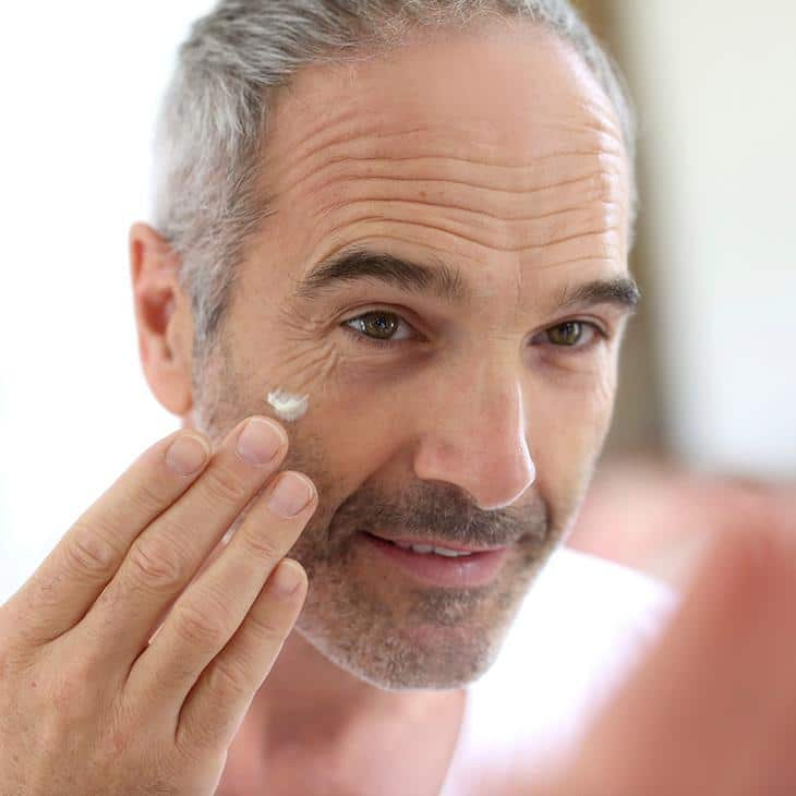 Male applying skin care cream to the face