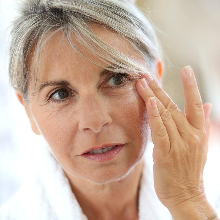 Mature female inspecting eye wrinkles