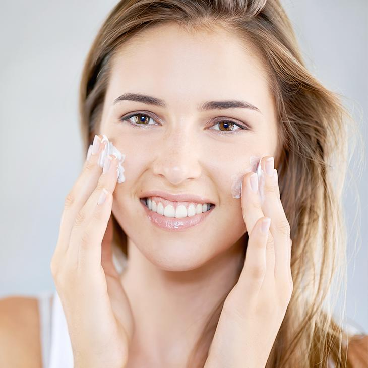 Female applying skin care cream to the face