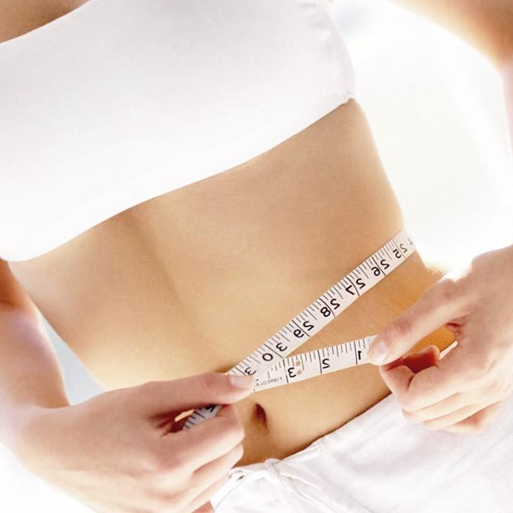 Female measuring slim waist